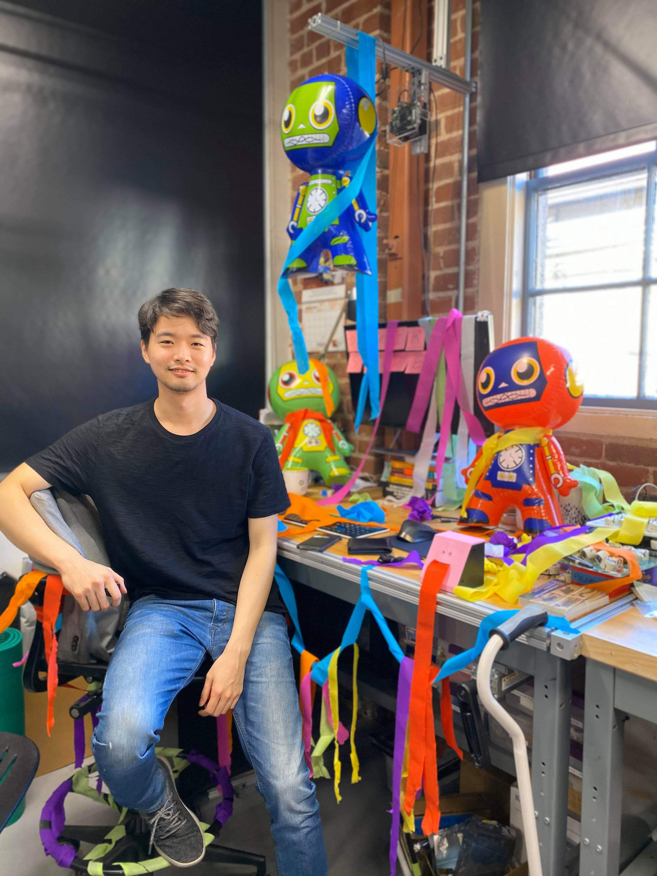picture of Lawrence standing in front of his desk full of colorful papers and inflatable robots.